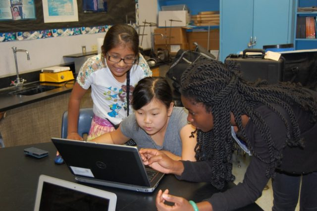 Three female students viewing laptop.